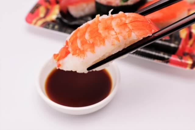 醤油につけられるエビのお寿司