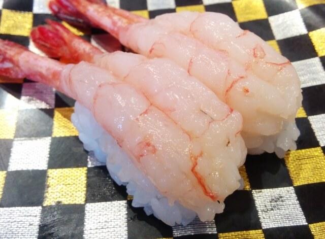 チェック模様の皿の上の甘エビのお寿司